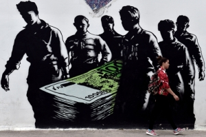 TOPSHOTS A young woman walks past a graffiti called 'Death of Euro' by French street artist Goin, in central Athens on June 19, 2015. The European Central Bank's decision-making governing council will hold an emergency session on June 19 to discuss a request from the Bank of Greece for an increase in liquidity to Greek banks. AFP PHOTO / ARIS MESSINIS