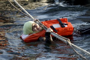 A refugee woman hangs on a rope as a half-sunken catamaran carrying around 150 refugees, most of them Syrians, arrives after crossing part of the Aegean sea from Turkey, on the Greek island of Lesbos, October 30, 2015. There were no casaulties amongst the refugees who were travelling on the catamaran, according to a Reuters witness. The death toll from drownings at sea has mounted recently as weather in the Aegean has taken a turn for the worse, turning wind-whipped sea corridors into deadly passages for thousands of refugees crossing from Turkey to Greece.  REUTERS/Giorgos Moutafis